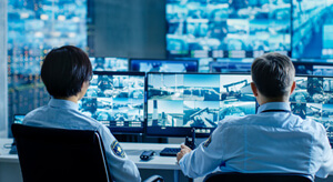 Image of two security personnel monitoring back to base security feeds.